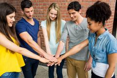 Stock Photo of Students putting hands together in unity