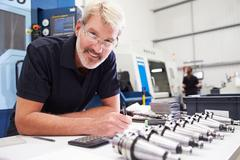 Engineer Planning Project With CNC Machinery In Background Stock Photos