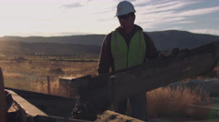 Construction worker pouring concrete at sunrise - stock footage