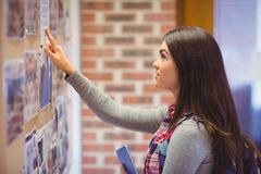 Young student pointing on notice board - stock photo
