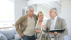 Senior couple with real-estate agent visiting house for sale - stock footage