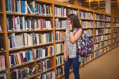 Young female student selecting book while talking on phone Stock Photos