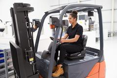 Female Fork Lift Truck Driver Working In Factory - stock photo