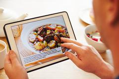Person At Breakfast Looking At Recipe App On Digital Tablet - stock photo
