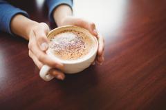 Woman having a cappuccino Stock Photos
