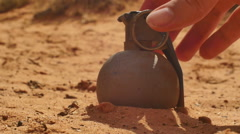 Picking up grenade in sand Stock Footage