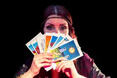 Portrait of fortune teller hiding mouth with tarot cards Stock Photos