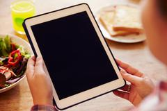 Person Looking At Digital Tablet Whilst Eating Lunch - stock photo