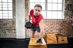Muscular man lifting dumbbell lean on a box Stock Photos