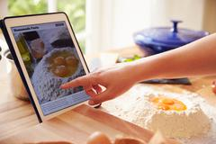 Person Following Pasta Recipe Using App On Digital Tablet - stock photo