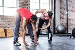 Female trainer assisting man with stretching exercises Stock Photos