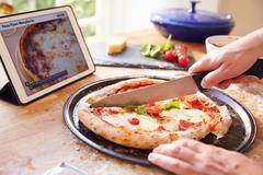 Person Following Pizza Recipe Using App On Digital Tablet Stock Photos