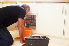Middle aged male plumber fixing a kitchen sink Stock Photos