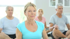 Group of senior people doing yoga exercises - stock footage