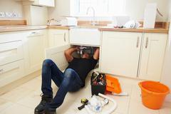 A plumber lying on his back to fix a kitchen sink Stock Photos