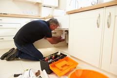 Male plumber fixing a kitchen sink Stock Photos