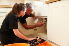 Plumber showing female apprentice how to fit a kitchen sink Stock Photos