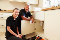 Portrait of male plumber with female apprentice in kitchen Stock Photos