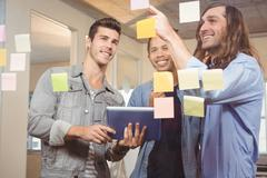 Businessmen smiling while looking at sticky notes Stock Photos