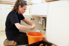 Female plumber preparing a pipe for a kitchen sink Stock Photos