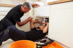 Plumber teaching an apprentice to fix a kitchen sink - stock photo