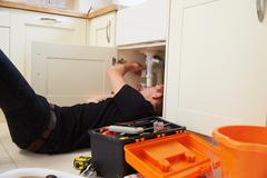 Apprentice plumber fixing the kitchen sink in a home Stock Photos