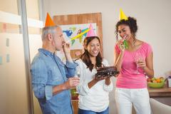 Stock Photo of Colleagues blowing party horn in birthday celebration of businesswoman