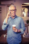 Creative businessman talking on mobile phone while holding disposable cup Stock Photos