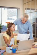Creative businesswoman showing document to colleague Stock Photos