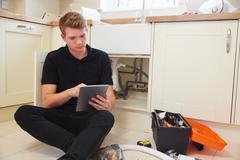 Young plumber with tablet computer fixing sink in kitchen - stock photo
