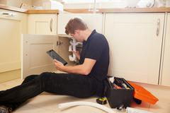 Plumber fixing sink in kitchen consulting tablet computer Stock Photos