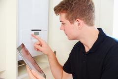 Young technician servicing a boiler, using tablet computer Stock Photos