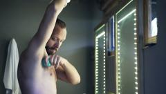 Young man in towel applying antiperspirant on his armpit in bathroom Stock Footage