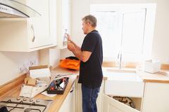 Man working on a new kitchen installation Stock Photos