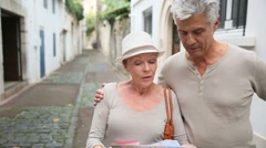Senior tourists walking in street with map Stock Footage