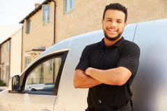 Portrait of mixed race tradesman by a van - stock photo