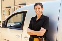 Portrait of young female trade worker standing by a van Stock Photos