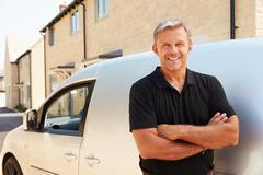 Portrait of middle aged tradesman standing by his van Stock Photos