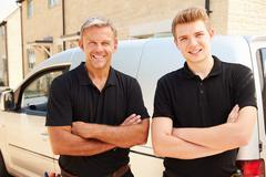 Portrait of a young and a middle aged tradesman by their van Stock Photos