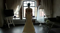 Bride at the window. Beautiful girl near the window with curtains. - stock footage