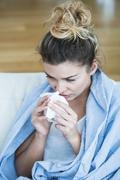 Feverish woman with tissue - stock photo