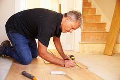 Man laying wood panel flooring during a house refurbishment - stock photo