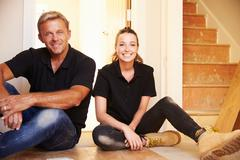 Man and woman sitting on floor during house refurbishment - stock photo