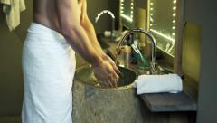 Young man in towel washing his hands in bathroom Stock Footage