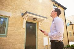 Male real estate agent looking up at a house exterior - stock photo