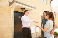 Real estate agent giving house keys to new property owners - stock photo