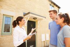 Young couple viewing a house with female real estate agent Stock Photos