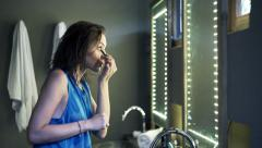 Pretty, young woman applying eye makeup in bathroom Stock Footage