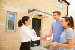Real estate agent shaking hands with new property owners Stock Photos