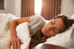 Woman Asleep In Bed As Sunlight Comes Through Curtains Stock Photos